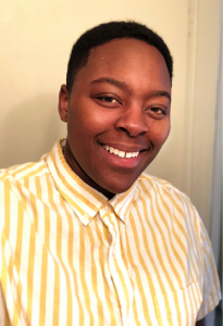 Smiling African American woman with short hair, wearing a yellow and white striped shirt.