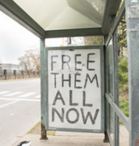 "graffitti saying ""Free Them All"""